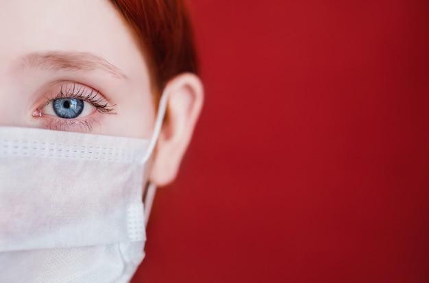 Garota ruiva com uma máscara médica sobre um fundo vermelho, médico da mulher, mulher com olhar intenso, europeu, metade do rosto, cabelo preso