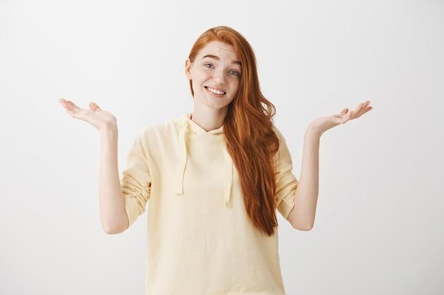 Garota ruiva confusa e indecisa dando de ombros com um sorriso forçado