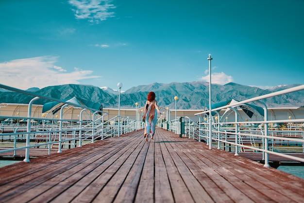 Garota ruiva corre ao longo do cais mulher em vestido longo esvoaçante cais de madeira marinho