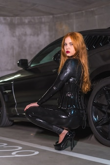 Garota ruiva de látex, blusa preta e calça justa de salto grande, agachada em um carro esporte na garagem