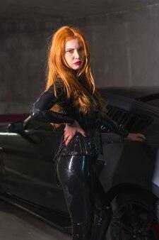 Garota ruiva de látex, blusa preta e calças justas, posou olhando para a câmera em um carro esporte em uma garagem
