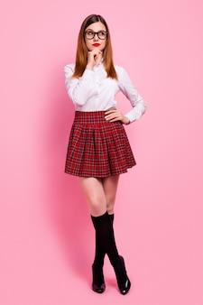 Garota ruiva de mente atraente pensando demais, fantasiando, isolada sobre um fundo de cor rosa