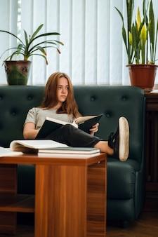 Garota ruiva de olhos azuis com expressão facial séria relaxando na biblioteca pública em um sofá com um livro aberto no colo e a perna em cima da mesa enquanto desvia o olhar.