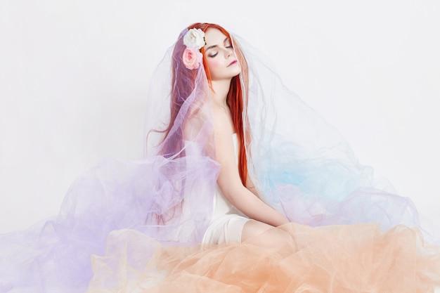 Garota ruiva de vestido colorido arejado claro senta-se