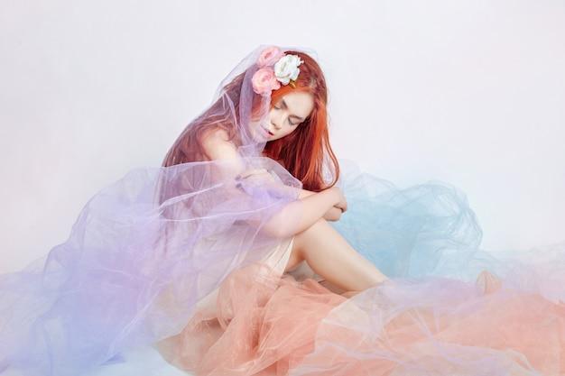 Garota ruiva de vestido colorido luz senta-se no chão