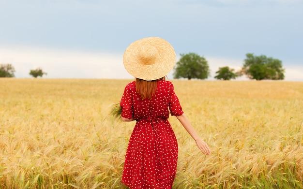 Garota ruiva de vestido vermelho no campo de trigo