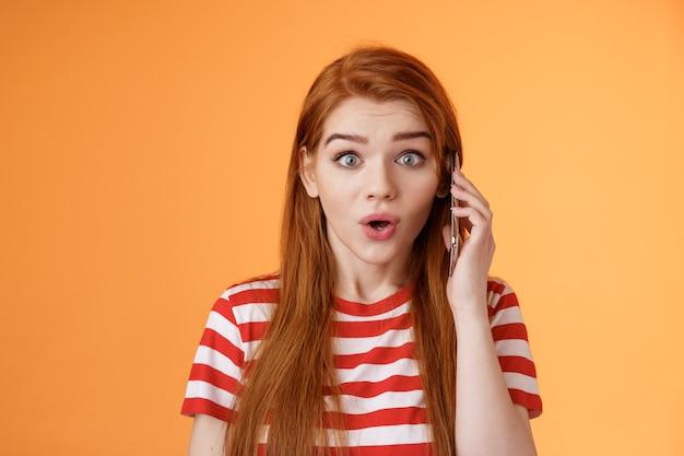 Garota ruiva divertida e emocionada descobriu notícias incríveis, falando ao telefone, segurando a orelha do smartphone, olhando a câmera surpresa, maravilhada, contando sobre uma promoção incrível, ficar surpreso com o fundo laranja