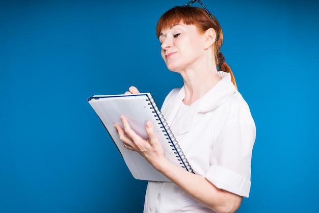 Garota ruiva em roupas de médico escreve em um caderno de um registro, isolado em um fundo azul
