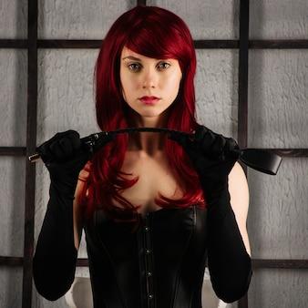 Garota ruiva em um espartilho de couro segura uma palmada. roupa bdsm