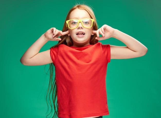 Garota ruiva em um estúdio de emoções de óculos amarelos estilo de vida infantil
