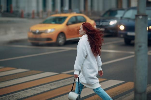 Garota ruiva em um jaleco branco e calça jeans azul atravessa a rua em uma passagem para pedestres