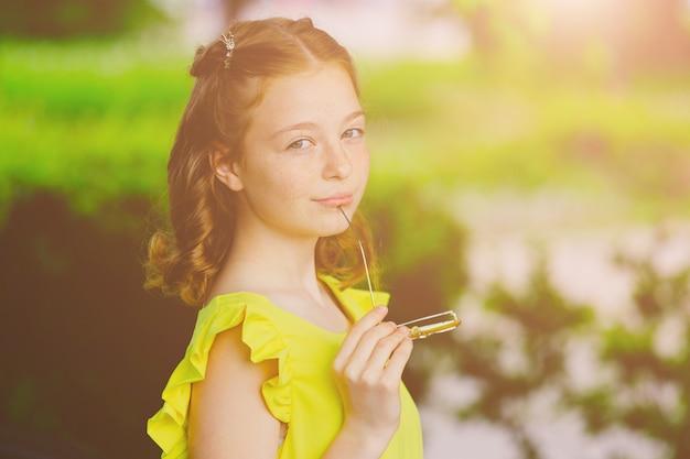 Garota ruiva em um vestido amarelo e óculos amarelos no parque no verão. foto de alta qualidade