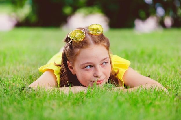 Garota ruiva em um vestido amarelo na grama do parque no verão. foto de alta qualidade