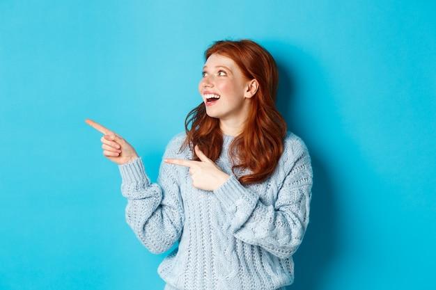 Garota ruiva empolgada de suéter, olhando e apontando o dedo para a esquerda, mostrando a oferta promocional ou logotipo, de pé sobre um fundo azul