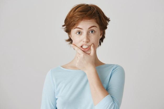 Garota ruiva engraçada posando contra a parede branca