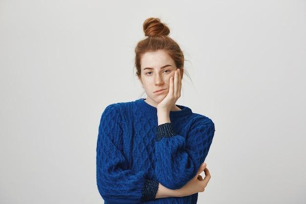 Garota ruiva entediada e relutante parecendo irritada