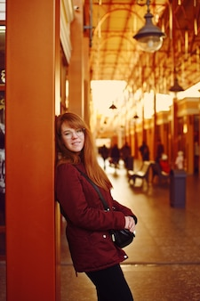 Garota ruiva esperando o trem na plataforma da estação ferroviária
