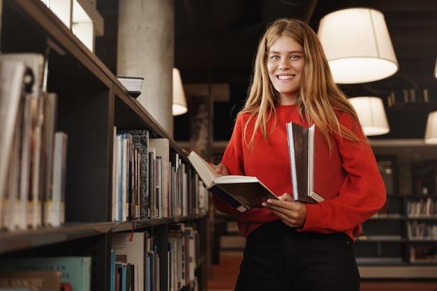 Garota ruiva, estudante em pé na biblioteca perto das prateleiras, lendo um livro e sorrindo.