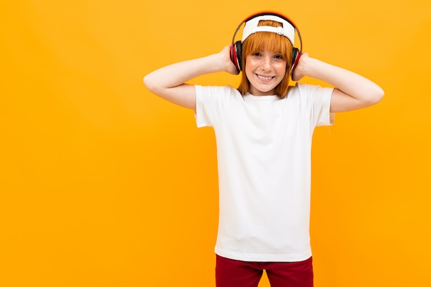 Garota ruiva europeia em uma camiseta branca com um telefone amarelo.