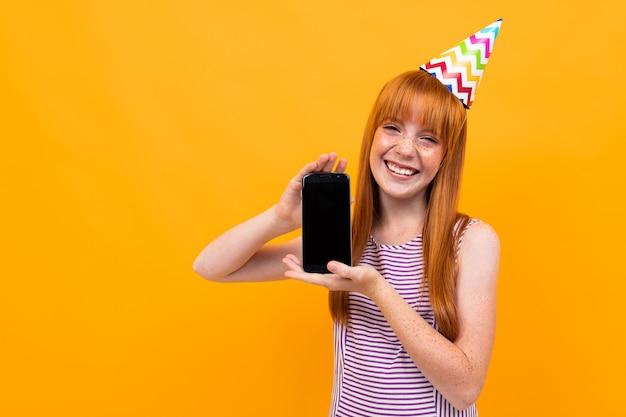 Garota ruiva europeia, segurando um telefone nas mãos com a tela para a frente em um amarelo