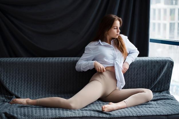 Garota ruiva europeia sentada no sofá olhando pela janela de casa