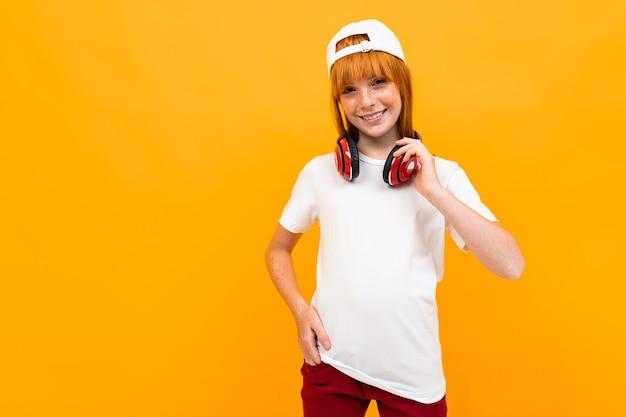 Garota ruiva europeia sorridente em uma camiseta branca com fones de ouvido