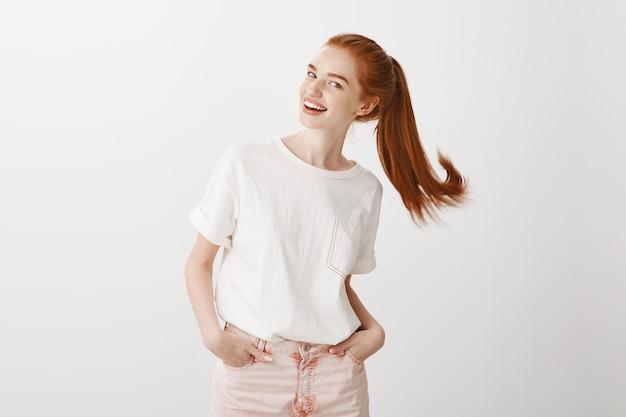 Garota ruiva feliz usando rabo de cavalo e sorrindo despreocupada