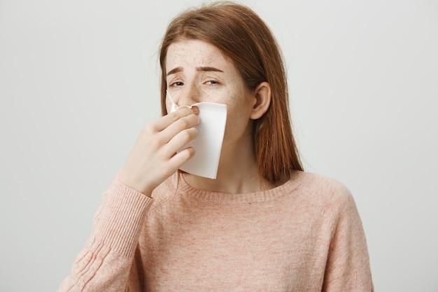 Garota ruiva fofa com alergia espirrando em guardanapo