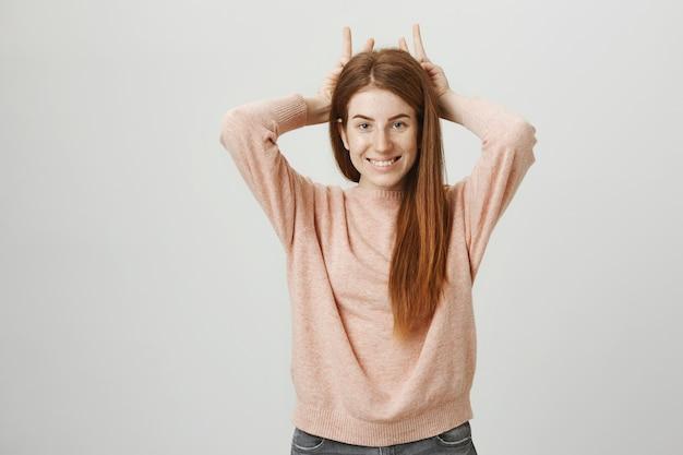 Garota ruiva fofa e idiota mostrando chifres acima da cabeça e sorrindo