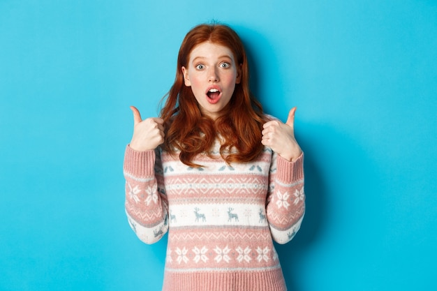 Garota ruiva impressionada em suéter mostrando polegar para cima, boca aberta fascinada, aprovar e gostar do produto, elogiar algo, de pé sobre um fundo azul.
