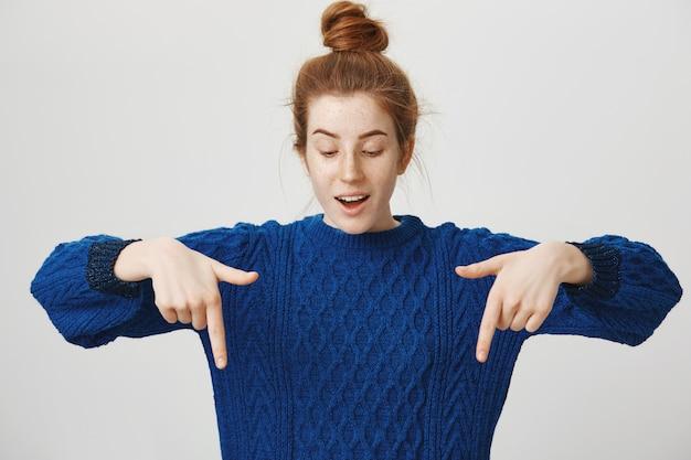 Garota ruiva intrigada apontando o dedo para baixo