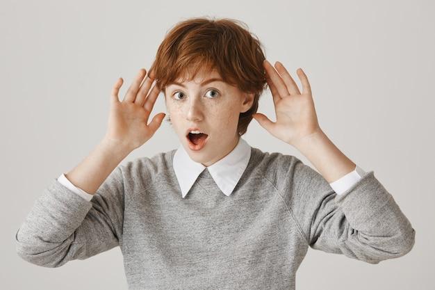 Garota ruiva intrigada com corte de cabelo curto posando contra a parede branca