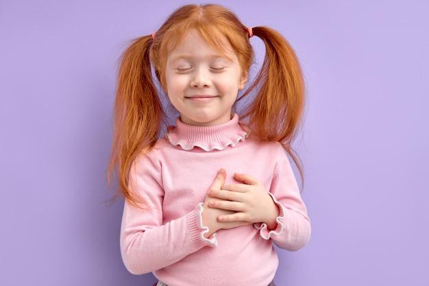 Garota ruiva legal segurando as mãos no peito, sentindo gratidão ou sonhando com os olhos fechados, isolados. copiar espaço
