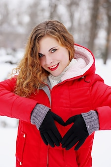 Garota ruiva mostrando um coração com as mãos no dia dos namorados