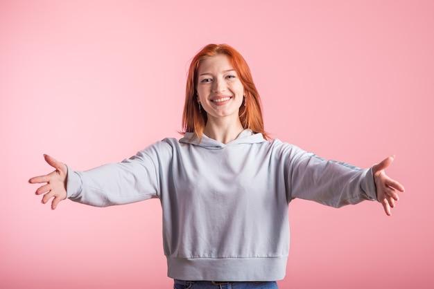 Garota ruiva mostrando um gesto de abraço em estúdio em fundo rosa