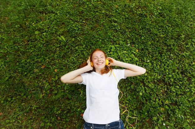 Garota ruiva ouve aulas com fones de ouvido. deitado na grama.