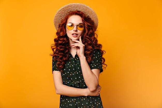 Garota ruiva pensativa, posando de óculos escuros e chapéu de palha. vista frontal da romântica senhora europeia isolada em fundo amarelo.