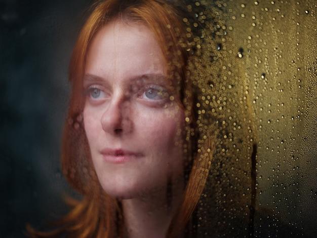 Garota ruiva perto de uma janela chuvosa