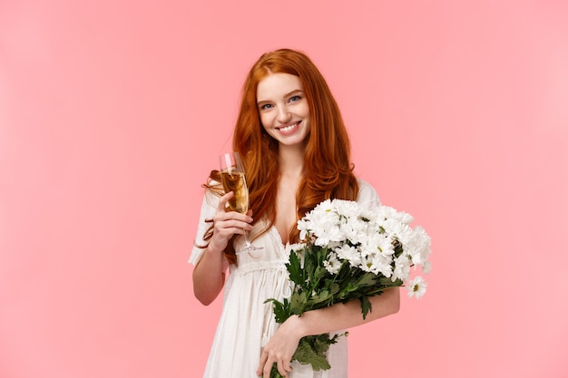 Garota ruiva romântica com lindo buquê floral vestido branco, segurando o copo de champanhe e sorrindo