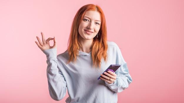 Garota ruiva segurando um celular e mostrando um gesto de ok no estúdio em um fundo rosa