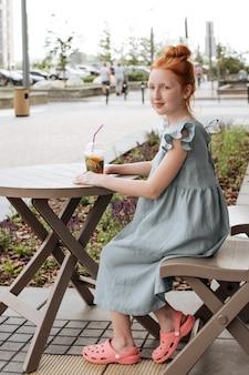 Garota ruiva sentada em um café de verão com um copo de limonada.