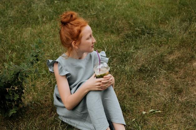 Garota ruiva sentada na grama com limonada nas mãos.