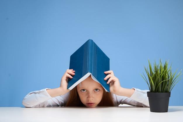 Garota ruiva sentada na mesa da escola livro na educação de mãos