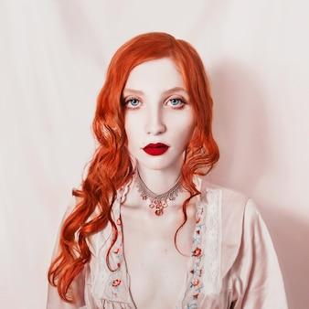 Garota ruiva sexy com os cabelos reunidos em um rabo de cavalo, segurando uma flor lilás nas mãos