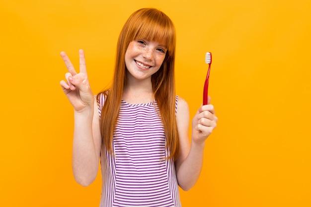 Garota ruiva sorri e segura uma escova de dentes nas mãos, sobre um fundo amarelo