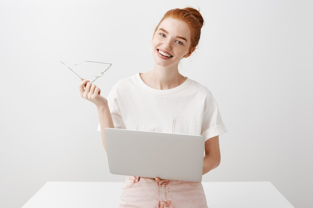 Garota ruiva sorridente usando laptop e olhando