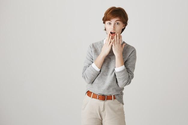 Garota ruiva surpresa e divertida com corte de cabelo curto posando contra a parede branca