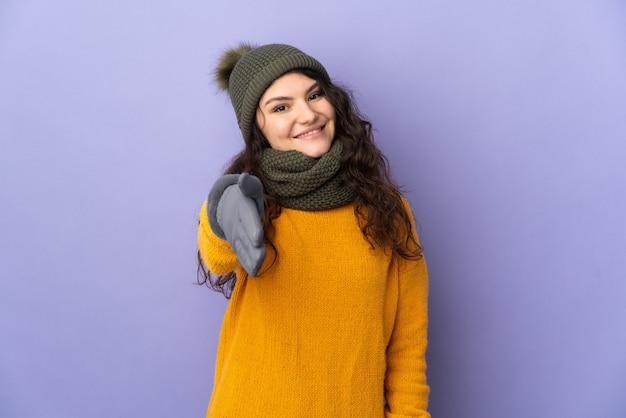 Garota russa adolescente com chapéu de inverno isolada em fundo roxo apertando as mãos para fechar um bom negócio