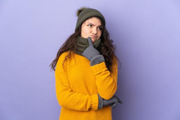 Garota russa adolescente com chapéu de inverno isolada em um fundo roxo tendo dúvidas enquanto olha para cima