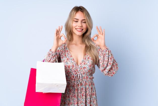 Garota russa adolescente com sacola de compras isolada em um fundo azul em pose zen